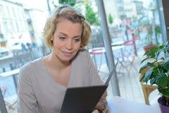 Όμορφη συνεδρίαση γυναικών στον πίνακα στις επιλογές ανάγνωσης καφέδων Στοκ φωτογραφία με δικαίωμα ελεύθερης χρήσης