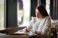 Όμορφη συνεδρίαση γυναικών στο εστιατόριο και γράψιμο Στοκ Εικόνες