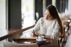 Όμορφη συνεδρίαση γυναικών στο εστιατόριο και γράψιμο Στοκ φωτογραφία με δικαίωμα ελεύθερης χρήσης