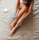 Όμορφη συνεδρίαση γυναικών στο κρεβάτι και εφαρμογή της κρέμας στα πόδια Στοκ εικόνα με δικαίωμα ελεύθερης χρήσης