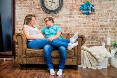 Όμορφη συνεδρίαση εγκύων γυναικών και ατόμων κοντά στον τοίχο Στοκ Εικόνες