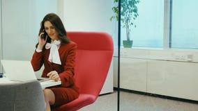 Όμορφη συνεδρίαση επιχειρηματιών σε μια κόκκινη καρέκλα που μιλά στο τηλέφωνο φιλμ μικρού μήκους