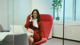 Όμορφη συνεδρίαση επιχειρηματιών σε μια κόκκινη καρέκλα που μιλά στο τηλέφωνο απόθεμα βίντεο
