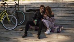 Όμορφη συνεδρίαση ζευγών αγάπης στα σκαλοπάτια και κατανάλωση croissants, καφές κατανάλωσης υπαίθρια, που κάθεται στο καρό απόθεμα βίντεο