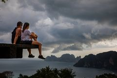 Όμορφη συνεδρίαση ζευγών στην ξύλινη πλατφόρμα με Phi Phi τις απόψεις νησιών και το νεφελώδη ουρανό στοκ φωτογραφία με δικαίωμα ελεύθερης χρήσης
