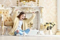 Όμορφη συνεδρίαση κοριτσιών εφήβων στο πάτωμα και χρησιμοποίηση του lap-top Στοκ Φωτογραφίες