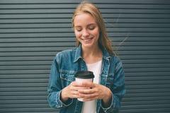 Όμορφη συνεδρίαση κοριτσιών στην οδό με τον καφέ και τη χαλάρωση πρωινού Στοκ Εικόνες