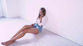 Όμορφη συνεδρίαση κοριτσιών στο πάτωμα σε ένα άσπρο δωμάτιο που μιλά στο τηλέφωνο φιλμ μικρού μήκους