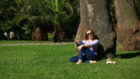 Όμορφη συνεδρίαση γυναικών κάτω από έναν φοίνικα και ξεφύλλισμα του Διαδικτύου σε ένα smartphone φιλμ μικρού μήκους