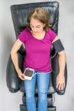 Όμορφη συνεδρίαση γυναικών Μεσαίωνα στη μαύρη πολυθρόνα δέρματος recliner Έλεγχος της πίεσης του αίματος που χρησιμοποιεί τη φορη Στοκ Φωτογραφία