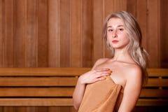 Όμορφη συνεδρίαση γυναικών που χαλαρώνουν σε μια ξύλινη καφετιά πετσέτα σαουνών Στοκ φωτογραφία με δικαίωμα ελεύθερης χρήσης