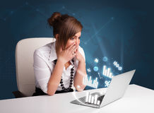Όμορφη συνεδρίαση γυναικών στο γραφείο και δακτυλογράφηση στο lap-top με τα διαγράμματα Στοκ εικόνα με δικαίωμα ελεύθερης χρήσης
