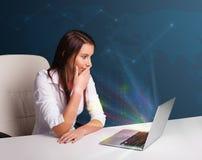 Όμορφη συνεδρίαση γυναικών στο γραφείο και δακτυλογράφηση στο lap-top με το abstra Στοκ Εικόνες