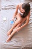 Όμορφη συνεδρίαση γυναικών στο κρεβάτι και εφαρμογή της κρέμας στα πόδια Στοκ Εικόνες