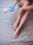 Όμορφη συνεδρίαση γυναικών στο κρεβάτι και εφαρμογή της κρέμας στα πόδια Στοκ Φωτογραφίες