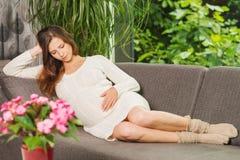 Όμορφη συνεδρίαση γυναικών pregnangt στον καναπέ στοκ εικόνες με δικαίωμα ελεύθερης χρήσης