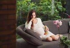 Όμορφη συνεδρίαση γυναικών pregnangt στον καναπέ στοκ φωτογραφία με δικαίωμα ελεύθερης χρήσης