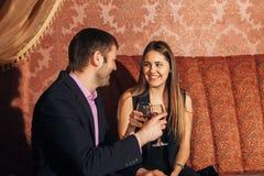 Όμορφη συνεδρίαση ζευγών σε ένα φανταχτερό εστιατόριο και ομιλία Στοκ Φωτογραφίες