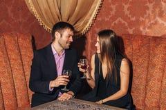 Όμορφη συνεδρίαση ζευγών σε ένα φανταχτερό εστιατόριο και ομιλία Στοκ Εικόνα