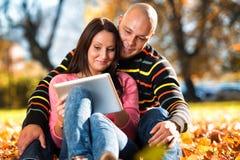 Όμορφη συνεδρίαση ζεύγους στο πάρκο και χρησιμοποίηση του υπολογιστή ταμπλετών Στοκ φωτογραφία με δικαίωμα ελεύθερης χρήσης