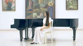 Όμορφη συνεδρίαση κοριτσιών κοντά στο πιάνο απόθεμα βίντεο