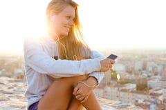 Όμορφη συνεδρίαση κοριτσιών στη στέγη και άκουσμα τη μουσική Στοκ Εικόνες