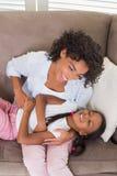 Όμορφη συνεδρίαση μητέρων στη tickling κόρη καναπέδων Στοκ φωτογραφία με δικαίωμα ελεύθερης χρήσης