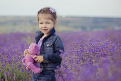 Όμορφη συνεδρίαση νέων κοριτσιών lavender στον τομέα στο συμπαθητικό καπέλο boater με το πορφυρό λουλούδι σε το Στοκ Φωτογραφία