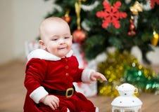 Όμορφη συνεδρίαση παιδιών μπροστά από το χριστουγεννιάτικο δέντρο στοκ εικόνα
