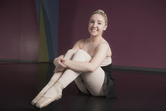 Όμορφη συνεδρίαση ballerina και χαμόγελο στη κάμερα στοκ εικόνες
