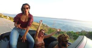 Όμορφη συνεδρίαση brunette στην κουκούλα μετατρέψιμου οδηγώντας με τους φίλους της απόθεμα βίντεο