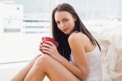 Όμορφη συνεδρίαση brunette στο πάτωμα με την κούπα Στοκ εικόνα με δικαίωμα ελεύθερης χρήσης