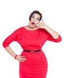 Όμορφη συν το μέγεθος η γυναίκα στο κόκκινο φόρεμα με τη χειρονομία κλήσης απομονώνει Στοκ Εικόνα