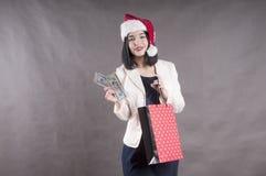 Όμορφη συσκευασία santa κοριτσιών ΚΑΠ που ψωνίζει με μια δέσμη των δολαρίων Στοκ εικόνα με δικαίωμα ελεύθερης χρήσης