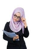 Όμορφη σύγχρονη νέα ασιατική μουσουλμανική επιχειρησιακή γυναίκα που εξετάζει τις εκθέσεις στοκ φωτογραφία