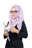 Όμορφη σύγχρονη νέα ασιατική μουσουλμανική επιχειρησιακή γυναίκα που κρατά ένα φλυτζάνι και τις εκθέσεις καφέ στοκ εικόνα
