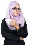 Όμορφη σύγχρονη νέα ασιατική μουσουλμανική επιχειρησιακή γυναίκα που κρατά ένα άσπρο φλυτζάνι καφέ στοκ φωτογραφία