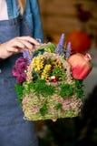 Όμορφη σύνθεση των λουλουδιών στα χέρια του ανθοκόμου στοκ εικόνα