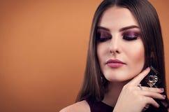 Όμορφη τέλεια σύνθεση γυναικών που φορά τα κοσμήματα στο καφετί υπόβαθρο στοκ φωτογραφίες με δικαίωμα ελεύθερης χρήσης