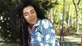 Όμορφη ταλάντευση γυναικών χαμόγελου στην ταλάντευση στο πάρκο απόθεμα βίντεο