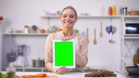 Όμορφη ταμπλέτα εκμετάλλευσης κοριτσιών με την πράσινη οθόνη, εύκολη κινητή εφαρμογή μαγειρέματος απόθεμα βίντεο