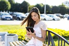 Όμορφη ταμπλέτα εκμετάλλευσης κοριτσιών, φωτεινή ηλιόλουστη ημέρα, σε έναν πάγκο, αστική ζωή ύφους μόδας Διαβάστε τα ε-βιβλία, κά Στοκ εικόνες με δικαίωμα ελεύθερης χρήσης