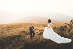 Όμορφη τοποθέτηση γαμήλιων ζευγών πάνω από ένα βουνό στο ηλιοβασίλεμα Στοκ Εικόνα