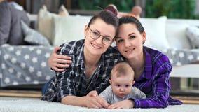 Όμορφη τοποθέτηση γονέων hipster δύο θηλυκή με λίγο χαριτωμένο μωρό που βρίσκεται στο πάτωμα που εξετάζει τη κάμερα απόθεμα βίντεο