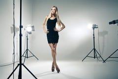 Όμορφη τοποθέτηση γυναικών στο στούντιο στις ελαφριές λάμψεις Στοκ Εικόνες