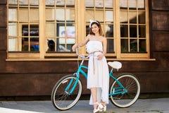 Όμορφη τοποθέτηση κοριτσιών κοντά στο τυρκουάζ ποδήλατο μπροστά από έναν καφέ Στοκ Φωτογραφία