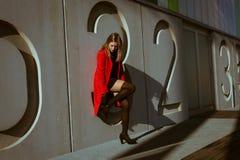 Όμορφη τοποθέτηση κοριτσιών με το κόκκινο παλτό στοκ εικόνα