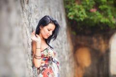 Όμορφη τοποθέτηση κοριτσιών brunette κοντά στον τοίχο βράχου Στοκ Φωτογραφία
