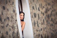 Όμορφη τοποθέτηση κοριτσιών brunette κοντά στον τοίχο βράχου Στοκ Φωτογραφίες