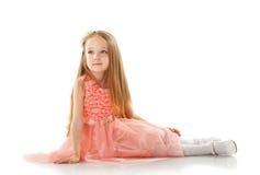 Όμορφη τοποθέτηση μικρών κοριτσιών στο έξυπνο ρόδινο φόρεμα στοκ εικόνες